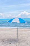 Blue beach umbrella on a sunny day Stock Photos