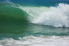 Blue Beach wave. Foamy white wave crashing on a sandy beach shore beside a dark blue sea Royalty Free Stock Images