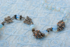 Blue beads on blue lace. Fragment of blue beads on blue lace background Stock Photo