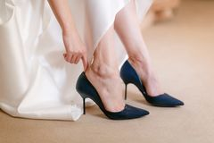 Blue beautiful bride shoes- wedding details. close up view woman Puts on wedding shoes. Stock Photo