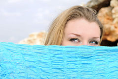Blue beautiful eyes of the girl behind  blue scarf Royalty Free Stock Images