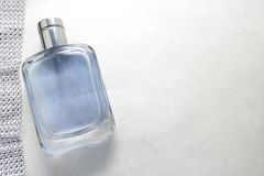 Blue beautiful glass transparent fashionable glamorous bottle of cologne, perfume and ribbon of sparkling rhinestones, diamonds an. D a place for a simple text Royalty Free Stock Images