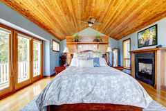 Blue bedroom with wood ceiling and fireplace Royalty Free Stock Images