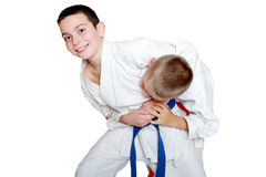 With a blue belt athlete did capture an athlete's head with an orange belt. With a blue belt sportsman did capture an athlete's head with an orange belt Stock Photos
