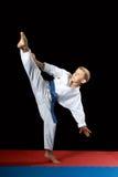 With a blue belt an athlete doing kick mawashi-geri on a black background Stock Photos