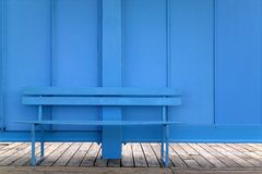 Blue bench. Against a blue wall Royalty Free Stock Photo