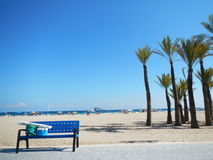 Blue Bench by the Beach. Blue Bus Stop Bench with a Beach goers belongings Stock Image