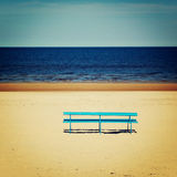 Blue bench on the empty beach - vintage photo. Picnic bench and spring seascape - retro filter. Royalty Free Stock Photo