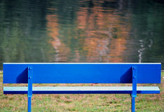 Blue bench. A blue bench facing a small lake Stock Photography