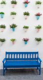 Blue bench with flower pots. On background wall Stock Photography