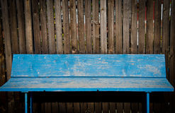 Blue bench. In front of brown fence Royalty Free Stock Image