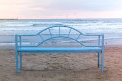 Blue bench on the sandy beach at sunset. Convenient infrastructure for relaxing by the sea. Sea wave. Blue bench on the sandy beach. Convenient infrastructure stock photography