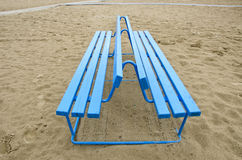 Blue bench on sea beach sand Stock Image