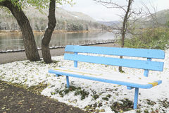 Blue bench at the snow on the banks of the river Royalty Free Stock Photos