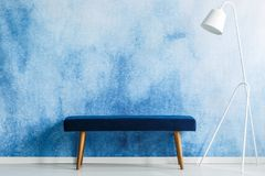 Blue bench and white lamp set on aquarelle wall in a waiting room interior. Place your product stock photography