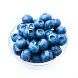 Blue berries. In a glass cup, isolated on white royalty free stock photography