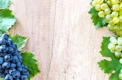 Blue Berries and Green Grapes on Beige Wooden Surface royalty free stock photo
