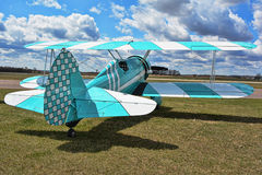 Blue Bi-Plane. Baby blue and white bi-plane parked in a grassy area at a small airport Stock Photography