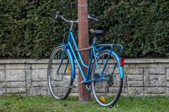 Blue bicycle against a pole, France. Blue bicycle against a pole in France Royalty Free Stock Photo