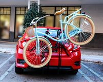 Blue bicycle with basket fastened to back of red sports car. Parked in front of shops Stock Image