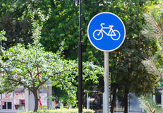 Blue bicycle lane sign with trees background Royalty Free Stock Photo