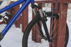 Blue bicycle locked to wooden bike rack during winter Stock Image