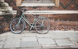 Blue Bicycle Parked on Brown Bricked Wall Royalty Free Stock Photography