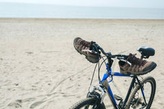 Blue bicycle parked near the sea standing on the beach Royalty Free Stock Image
