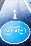 Bicycle sign on pavement road. Blue bicycle sign on pavement road  after rain Stock Photography