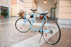 Blue bicycle on street in background of shops Royalty Free Stock Image