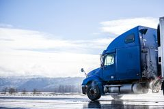 Blue big rig long haul semi truck with reefer semi trailer running on winter wet road with melting snow and water dust. Big rig pro long haul blue semi truck stock images