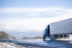 Blue big rig long haul semi truck transporting cargo in refrigerated semi trailer running on wet winter road with melting snow. Big rig pro long haul blue semi stock photography