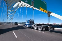 Blue big rig semi truck with day cab and flat bed semi trailer d stock images