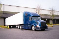 Dark blue big rig semi truck with trailer in warehouse dock load Royalty Free Stock Photos