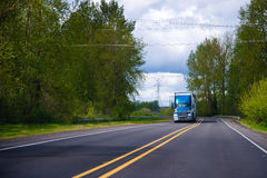 Blue big rig semi truck on green road with trees Stock Photography