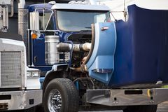 Blue big rig semi truck with open hood standing on the parking lot for repair engine and service work. Blue classic American bonnet big rig semi truck with open stock photo