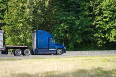 Blue big rig semi truck profile going with semi trailer on the r stock images