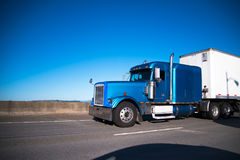 Blue big rig semi truck with semi trailer moving ahead by wide h Stock Image