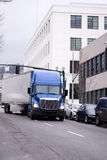 Blue big rig semi truck with trailer turn on the street of urban Royalty Free Stock Photos