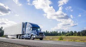 Free Blue Big Rig Semi Truck With Grille Guard Trabsporting Frozen Cargo In Refrigerator Semi Trailer With Skirt Spoiler Running On The Royalty Free Stock Photography - 157624897