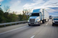 Semi-truck tractor trailer on the highway royalty free stock photo