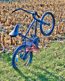 A blue bike leaning backward by itself with a flag in the spokes in a field. A blue bike standing on its bike tire with a flag in the spokes in a field Royalty Free Stock Images