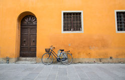 Blue Bike with Yellow Chain on Orange Wall Stock Image