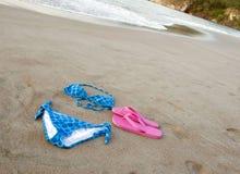 Blue bikini and shoes on tropical beach. Blue spotted bikini with pink shoes on tropical beach Royalty Free Stock Photo