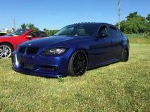 Blue bimmer with black rims at a car meet stock photos