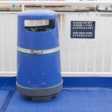 Blue bin on deck of cruise liner. Do not throw litter overboard Stock Images