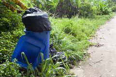 Blue bin with trash over. A blue bin with trash over the side. ฺbeside of road, with nature in countryside stock photography