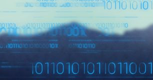 Blue binary code against blurry mountain. Digital composite of Blue binary code against blurry mountain Royalty Free Stock Photography