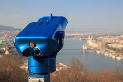 Blue binoculars and defocused panorama view of the famous Hungarian Parliament across the river Danube, Budapest.  royalty free stock photos