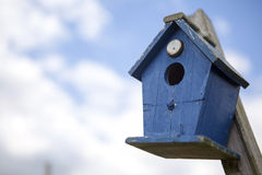Blue bird house in front of cloudy sky Royalty Free Stock Photo